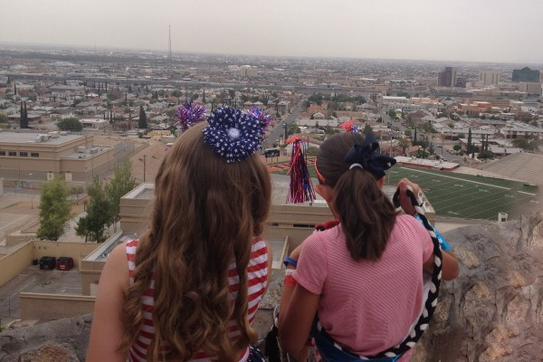 Two young girls dressed up to celebrate the Fourth of July take in the scenic view of El Paso, Texas, and Juarez, Mexico, from Tom Lea Park on Rim Road. Photo credit: Kate Gannon