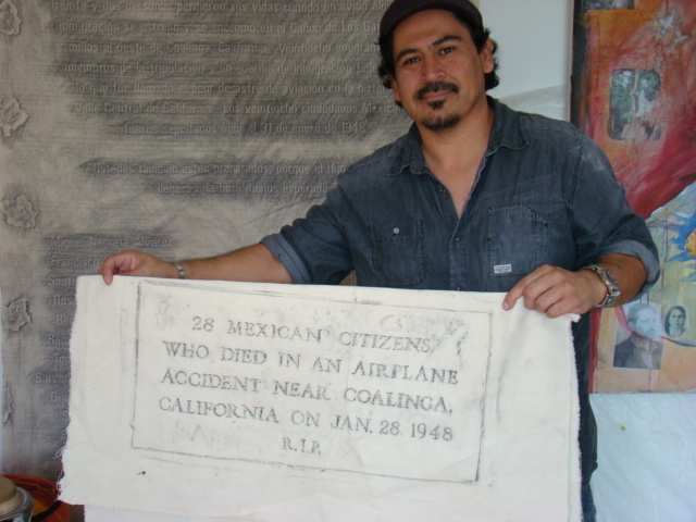 Tim Hernandez holds an imprint of the original headstone on a mass grave for victims of the Los Gatos plane crash that inspired Woody Guthrie's song Deportees.