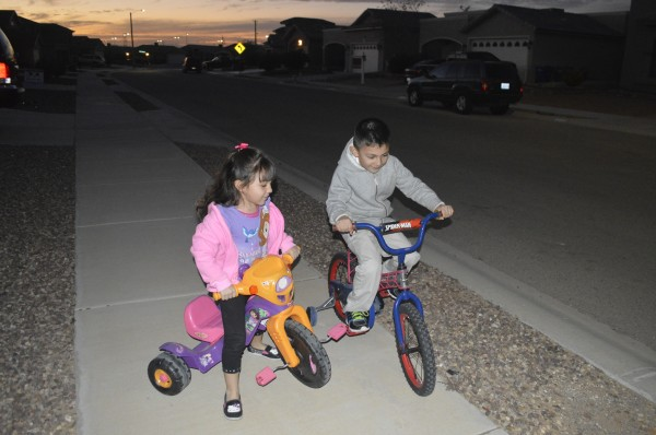The Velarde children stay active riding bikes outdoors for playtime.