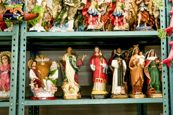 Statues of religious figures line green metal shelves in a shop window.