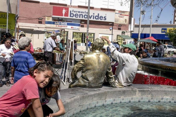 An image of a fountain in the historic center of Juarez, with a statue sitting on the rim of the fountain next to a man, and people going about their day nearby.