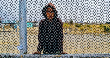A young boy peers through the fence between the U.S. and the village of Anapra, Mexico.