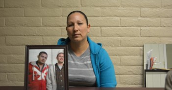 Griselda Reyna holding a framed picture of her two sons. Photo courtesy Lucia Murguia.