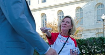 Theresa Anthony, senior director for Expo and Management for the National Confectioners Association, distributes candy packets to commuters at the Captiol South Metro Station with recently-published candy industry job statistics printed on them. SHFWire photo by Rebecca Anzel