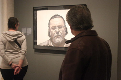 "Visitors at the Smithsonian's National Portrait Gallery look at Gaspar Enriquez's ""John"" portrait. Enriquez and 42 other artists' works were chosen from 2,500 submissions for the portrait competition that is held every three years. SHFWire photo by Luis Gonzalez"