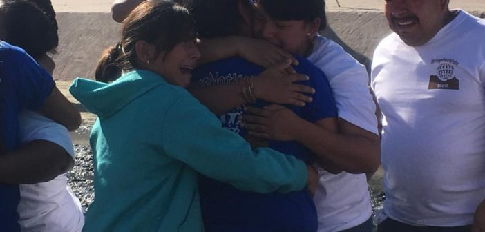 Brief reunion of families at border fence makes a point: walls divide, hugs unite