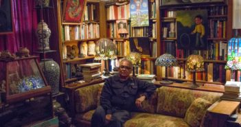 Juan Sandoval surrounded by his collection at his apartment. Photo by Andrew Rios for The Prospector.