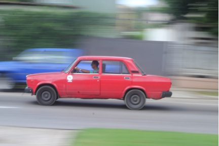 A car zooms by in Havana, Cuba.