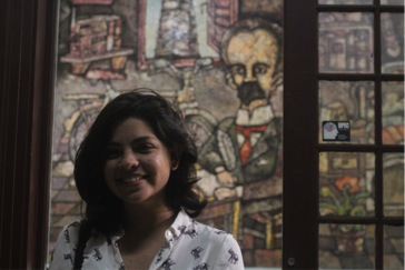 Daniella Fernandez in front of a mural of Independence hero Jose Marti inside the Instituto de Periodísmo Jose Martí in Havana.]