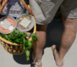 Farmers market attendee fills his grocery basket with products from One Grub Community. Photo credit: Kayla Melson
