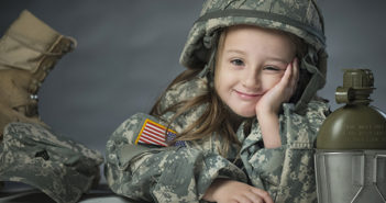Lily, daughter Army Sgt. James Newby, grins as she poses for portraits with her father's uniform items, March 18, 2015 on Fort Meade, Maryland. Photo credit: U.S. Air Force photo by Staff Sgt. Vernon Young Jr.