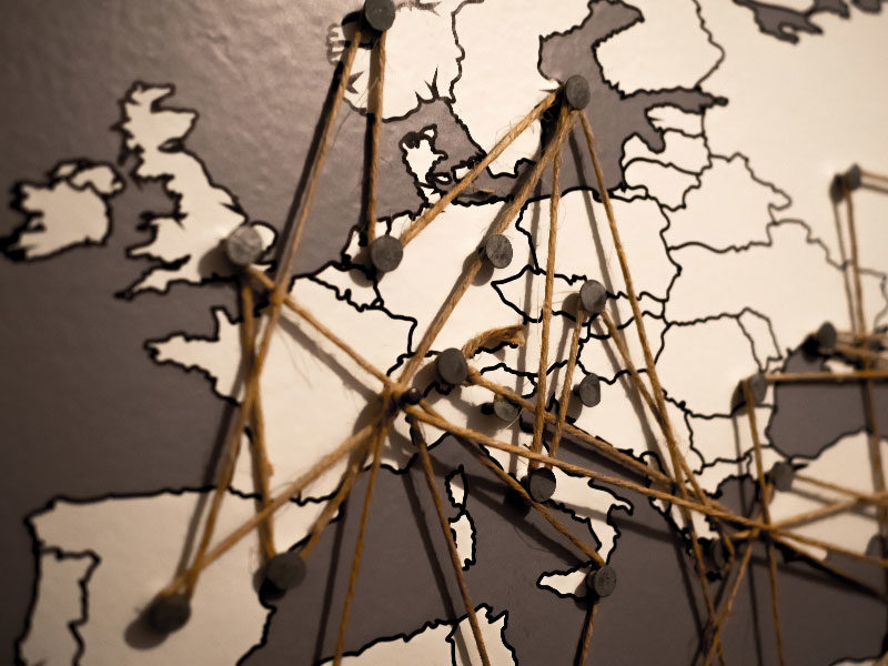 Illustration of criss-crossed string pinned to European countries.