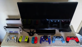 Video Game Controllers on top of furniture next to a TV and a Nintendo Switch Console.