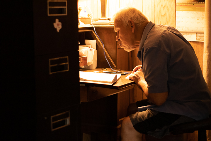 An elderly man sits at his desk looking over bills.