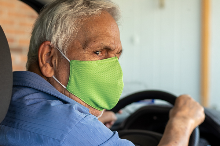 An elderly man looks behind him as he prepares to back out of the driveway of his home.