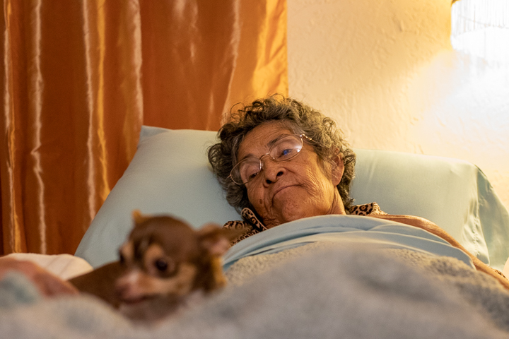 An elderly woman looks down past her dog while she lays in bed.