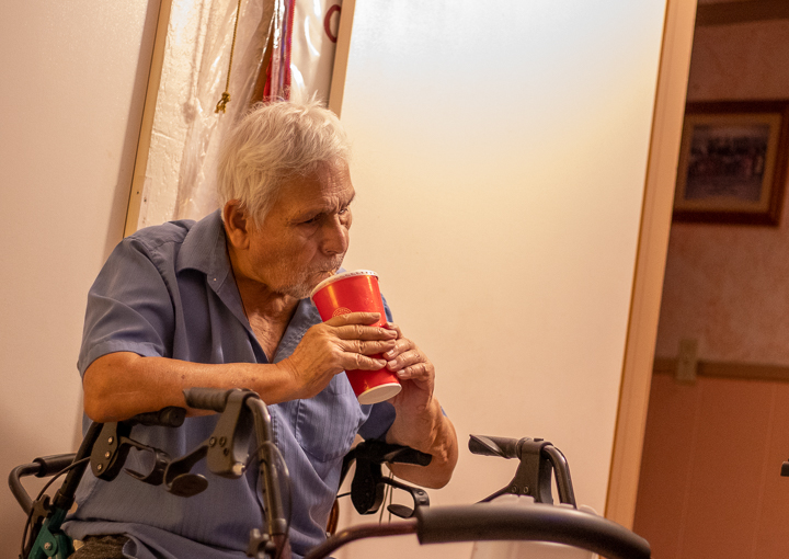 An elderly man sits drinking a coke out of a cup in his bedroom.