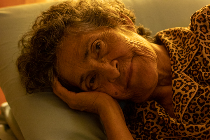 An elderly woman lays in bed smiling at the camera as she rests after surgery.