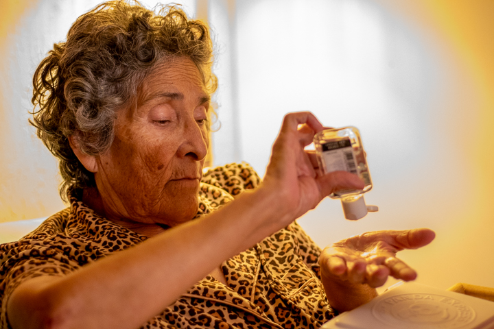 An elderly woman hand sanitizes her hands after eating lunch.