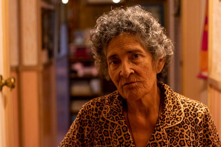An elderly woman walking down the hallway back into her bedroom.