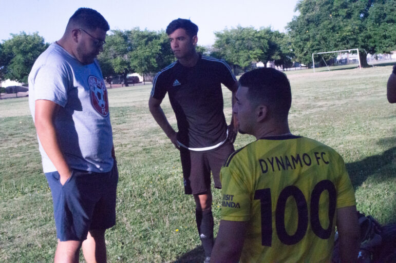 Before the Dynamo soccer team played, Coach Carlos Moreno is talking with two of his players, as the start warming up.