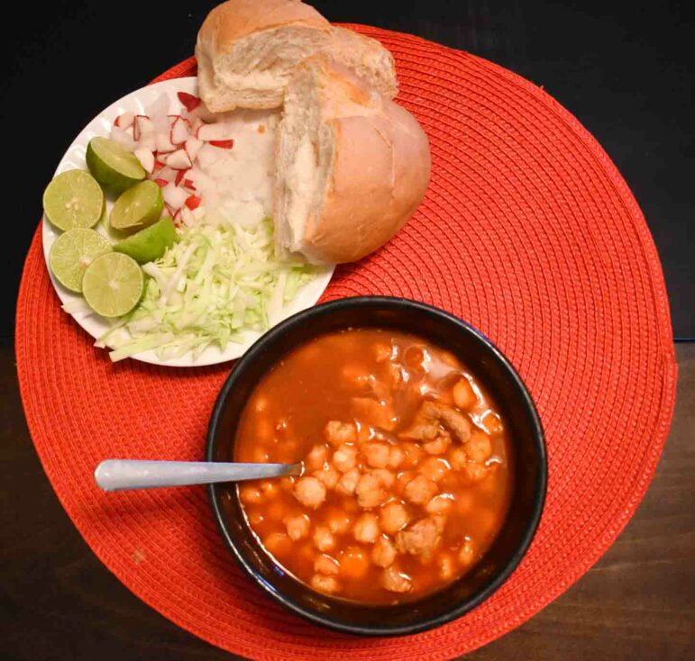 Pozole on the U.S.-Mexico border is typically prepared with a red sauce. It is served with a bolillo roll and garnished with shredded cabbage, radishes and lime. Photo by Emilia Zubia, Borderzine.com