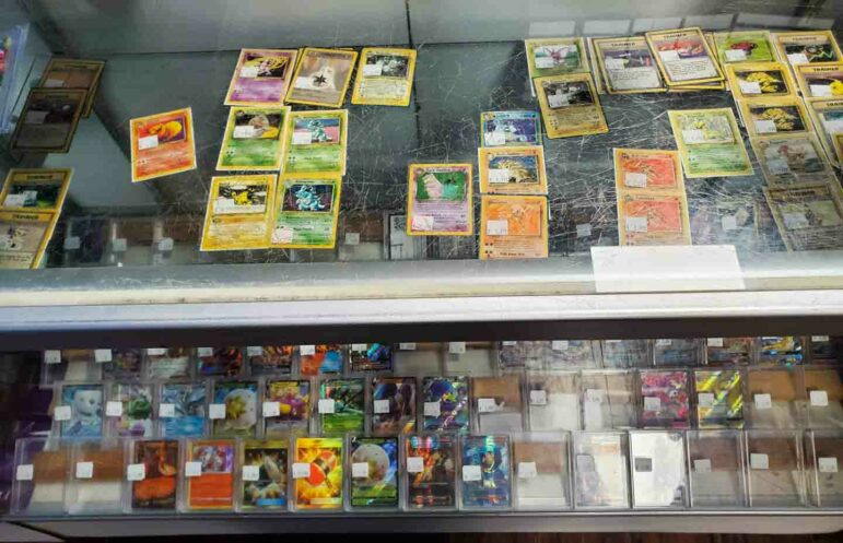 A case with Pokemon cards on display for sale.