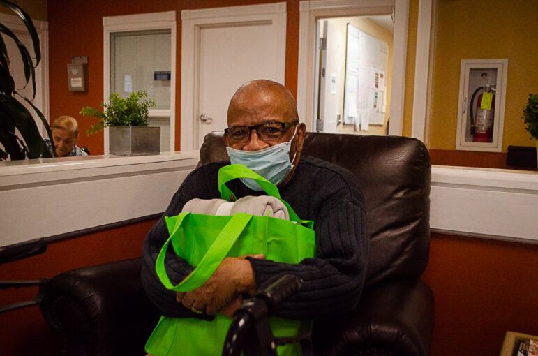 Oscar Hernandez poses with his 'Un abrazo' care package from the organization MYYC on February 13, 2021.