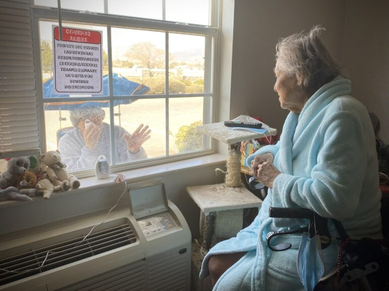Maria looks at her son, Raul Contreras, through the window of her assisting-living quarters during a visit to Sunridge at Cielo Vista.