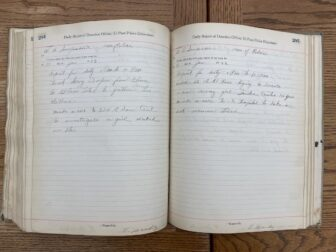 Open logbook full of notes on table.